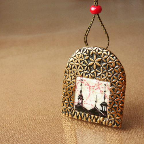 Bronzový náhrdelník s porcelánovým kabošonem. Na povrchu má sgrafito strukturu.