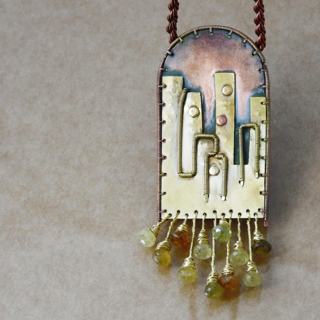 Neopakovatelný autorský drátovaný náhrdelník z mědi, mosazi a zelených granátů inspirovaný architekturou a životem velkoměst v rukou.