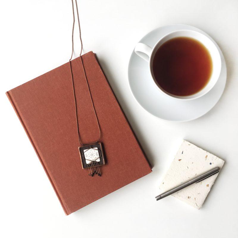 Neopakovatelný autorský náhrdelník z mědi a porcelánu s biologickým motivem v kompozici s knihou, čajem a perem.